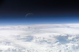 White cloud tops below with Earth's azure atmosphere blending into outer space, where a thin crescent moon hovers against the darkness