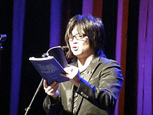 Standing Japanese man reading a book onstage at a microphone