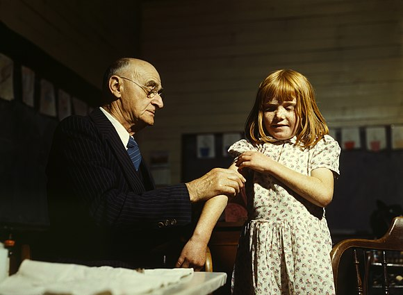 Doctor administering a typhoid vaccination at a school in San Augustine County, Texas, 1943 Typhoid inoculation2.jpg