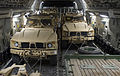 U.S. Air Force Senior Airman Pablo Aguilar, a loadmaster with the 816th Expeditionary Airlift Squadron, walks between two mine-resistant, ambush-protected vehicles in a C-17 Globemaster III aircraft at Kandahar 140125-F-XT249-053.jpg