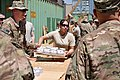 U.S. Air Force Staff Sgt. Christina Cordova, center, with Combined Joint Interagency Task Force 435, carries a tray of newly-formed fuel donuts to carry to the drying racks during an Operation Outreach 130728-F-JL359-028.jpg