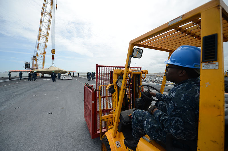 File:U.S. Navy Aviation Boatswain's Mate (Handling) 2nd Class Marvin Etienne watches as a Navy X-47B Unmanned Combat Air System demonstrator aircraft is loaded onto the flight deck of the aircraft carrier USS George 130506-N-FU443-277.jpg