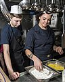 U.S. Navy Culinary Specialist Seaman Corbin Poinier, left, and Seaman Jessica Moffit prepare fish aboard the guided missile cruiser USS Philippine Sea (CG 58) June 30, 2014, in the Persian Gulf 140630-N-PJ969-023.jpg