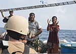 U.S. Sailors assigned to the guided missile destroyer USS Mason (DDG 87) give water to fishermen aboard a dhow during a visit, board, search and seizure operation Nov. 21, 2013, in the Gulf of Aden 131121-N-PW661-037.jpg