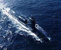 Black submarine running on surface carrying a cylindrical module on its back.