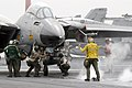 US Navy 030323-N-9593M-062 A flight deck director directs an F-14D Tomcat onto the one of four steam powered catapults as 'final checkers' conduct their inspections before the fighter is launched from the flight deck of USS Abr.jpg