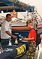 US Navy 031026-N-1159B-001 Engineman 2nd Class Michael Siorida gives Navy promotional material to a member of the Chosan unit of the Young Marines.jpg