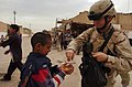 US Navy 050308-N-5319A-003 A U.S. Army Soldier assigned to 155BCT, Charlie Company, National Guard Unit from Tupelo, Miss., hands out candy to local children.jpg