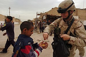 Iskandariya - A young U.S. soldier hands out candy to a local child in Iskandariya as locals look on