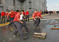US Navy 060107-N-6439C-084 Sailors from the Air Department run to a S-type eductor and a peri-jet eductor to de-water a 55-gallon drum during Damage Control (DC) Olympics aboard the amphibious assault ship USS Nassau (LHA 4).jpg