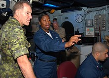 Air Traffic Controller 1st Class Erica Banks explains the SPN 43 Radar System to General Walter Natynczyk, Canadian chief of Defense Staff, in the amphibious air traffic control center aboard the amphibious assault ship USS Bonhomme Richard (LHD 6)