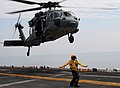 US Navy 100119-N-7508R-016 A landing signal enlisted (LSE) directs an MH-60S Sea Hawk helicopter assigned to Helicopter Sea Squadron (HSC) 22 to lift off from the multi-purpose amphibious assault ship USS Bataan (LHD 5).jpg