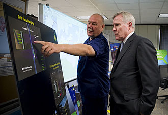 GIS and environmental governance - The Secretary of the US Navy, Ray Mabus is briefed on the Deepwater Horizon oil spill response. A web-based GIS is visible in the background. The NOAA-developed Environmental Response Management Application (ERMA) was designed to assist resource managers post-spill.