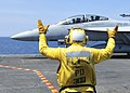 US Navy 100804-0569K-N-022 An aircraft director guides pilots assigned to the Checkmates of Strike Fighter Squadron (VFA) 211 into position aboard the aircraft carrier USS Enterprise (CVN 65).jpg