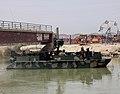 US Navy 100812-N-5472R-183 Sailors navigates under a low pedestrian bridge before landing security teams ashore.jpg