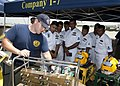 US Navy 110910-N-HA376-119 Navy Diver 2nd Class Wade Luoma, assigned to Mobile Diving and Salvage Unit (MDSU) 1, explains an oxygen regulator conso.jpg