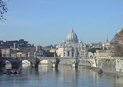 A view of Rome on a sunny afternoon looking along the river. A bridge crosses the river and beyond it is a hill on which the grey dome of St. Peter's rises above ancient buildings and dark pine trees. St. Peter's Basilica VATICAN