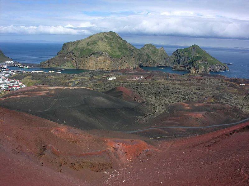 View of a town and some islands from the red rocks of a volcano, on the islands of Vestmannaeyjar, the Southern Region