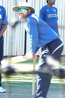 A man in the blue Indian cricket practice kit batting. Other cricketers in the same uniform can be seen standing around
