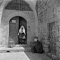 Vrouw en een zittende persoon, vermoedelijk bedelend, bij de toegangsdeur van de, Bestanddeelnr 255-0445.jpg