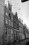 foto van Huis met halsgevel met gedeelde geruite vleugelstukken en een palmet in de afdekking