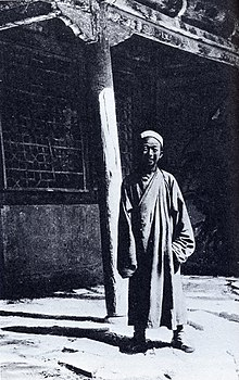 A black-and-white picture of an elderly Chinese man in front of a building