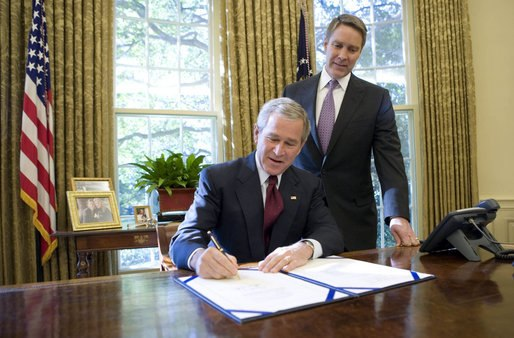With Sen. Bill Frist (R-Tenn.) looking on, President George W. Bush signs into law S-3728, the North Korea Nonproliferation Act of 2006, Friday, Oct. 13, 2006, in the Oval Office