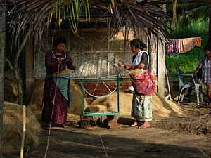 Two women spinning coconut fibre on small green loom outside a home