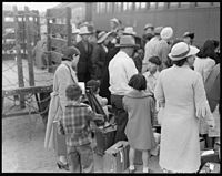Woodland, California. Farm families of Japanese ancestry waiting at the railroad station for the sp . . . - NARA - 537809