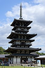 Three storied wooden pagoda with white walls. Additional pent roofs on every floor give the appearance of twice as many floors, i.e. six floors.