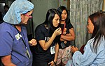 Yesi Paat, center left, an interpreter with Hope Worldwide, translates instructions from Jenni Hoermann, left, a registered nurse with the Latter-day Saint Charities, to an Indonesian patient before entering an 120603-N-GW695-001.jpg