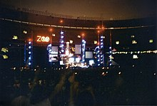 "An elaborate concert stage set bearing a logo that reads ""Zoo TV"", set in a dark stadium. Towers reach into the nighttime sky, illuminated in blue with red warning lights on top."