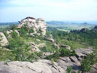 Tor (rock formation) Large, free-standing rock outcrop that rises abruptly from the surrounding smooth and gentle slopes of a rounded hill summit or ridge crest