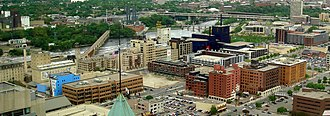 Mill District, Minneapolis - The Mill District, bounded on the northeast by the Mississippi River. Bridges seen are the I-35W Mississippi River bridge and Stone Arch Bridge