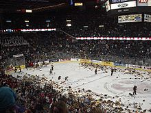 Wide angle shot of a hockey rink. Fans on all sides are throwing stuffed animals onto the ice where several hundred are piling up.