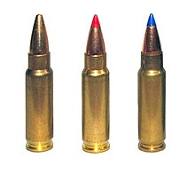 Photo of three 5.7×28mm cartridges as used in the P90. The left cartridge has a plain hollow tip, the center cartridge has a red plastic V-max tip, and the right cartridge has a blue plastic V-max tip.
