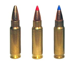 Tiga foto peluru 5,7 × 28 mm untuk olah raga menembak. The left cartridge has a plain hollow tip, the center cartridge has a red plastic V-max tip, and the right cartridge has a blue plastic V-max tip.