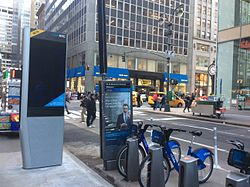 A Citi Bike pay station in Midtown Manhattan, with a few bikes shown at right. A LinkNYC booth for free internet and phone calls is located on the left.