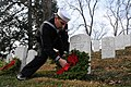 A Sailor places a holiday wreath on a grave at Arlington National Cemetery. (15842892160).jpg