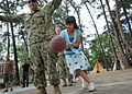 A girl at a Shepherd of the Hills Children's Foundation home in San Antonio, Philippines, dribbles a basketball around U.S. Navy Construction Electrician 1st Class Isaac Barajas, a member of a joint 130323-N-VN372-367.jpg