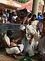 A grandfather feeding a Hindu baby her first solid food eating Annaprashana samskara rite-of-passage ceremony inside Shiva temple Kerala.jpg