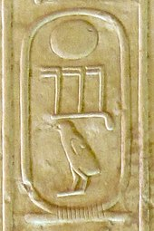 Three hieroglyphs inscribed on a cream-colored stone: a circle, beneath it three toes and a chick