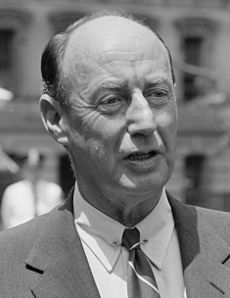 A man with receding dark hair wearing a black jacket, white shirt, and striped tie