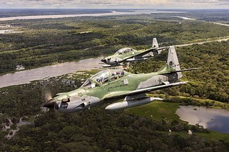 Military aircraft - Two Embraer EMB 314 Super Tucanos of the Brazilian Air Force fly over the Amazon rainforest.