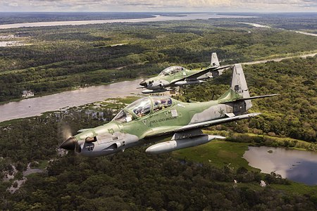 A pair of Brazilian Air Force Embraer A-29 Super Tucanos in flight over the Amazon Rainforest.
