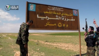 Al-Tawhid Brigade - Fighters of the al-Tawhid Brigade deface an image of President Bashar al-Assad on the road between Hama and Raqqa on 27 March 2013.