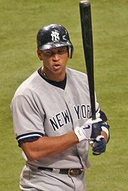 "A Hispanic man walking while shouting at someone out of the picture. His helmet is emblazoned with a white ""N"" and ""Y"" intertwined, and ""NEW YORK"" is stitched in black letters across his button-down jersey. The player is holding a black baseball bat almost vertically with black, gray, and white gloves."