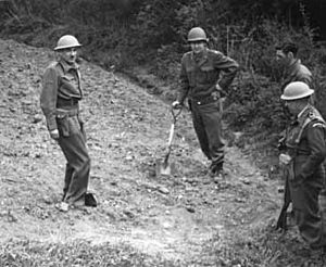 Four men in uniforms. One is leaning on a spade, and wearing an American helmet. Two others are wearing British helmets. A dark haired man has no helmet.