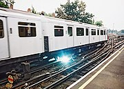 """Electricity arcs between the power rail and electrical pickup """"shoe"""" on a London Underground train"""