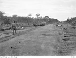 Parit Sulong Massacre - Wreckage of the 45th Indian Brigade still littered on both sides of the road at Parit Sulong on 26 September 1945. Some of the gear of some 150 Australian and Indian troops massacred by the Japanese can be seen on the left.